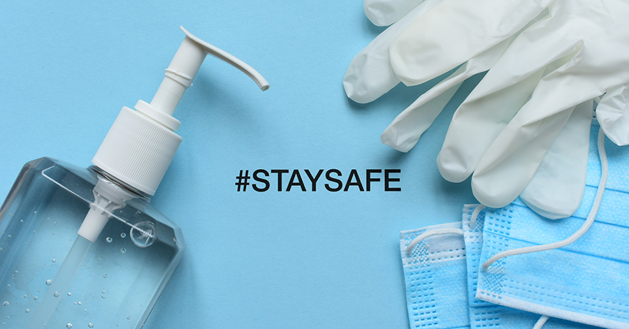 close up of gloves mask and handsanitizer, with the words staysafe in the middle